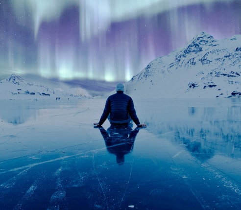 A man sitting in the middle of a frozen lake and admiring the Northern Lights