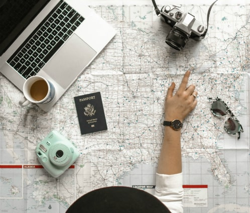 A woman is planning a route of her trip using a map