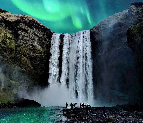 People admiring the Northern Lights near the Skogafoss Watefall, Iceland