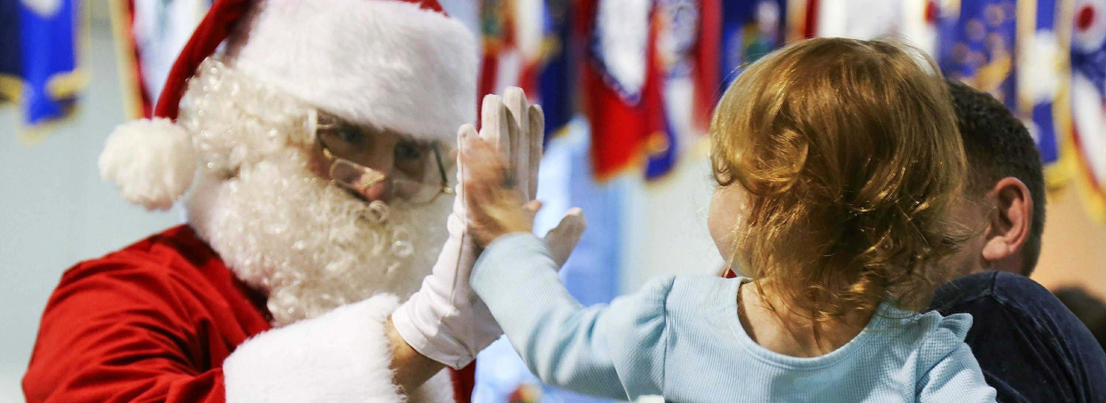 Santa Claus high-fives a small kid